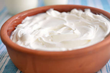 strained: Pot with strained yogurt closeup  Selective focus