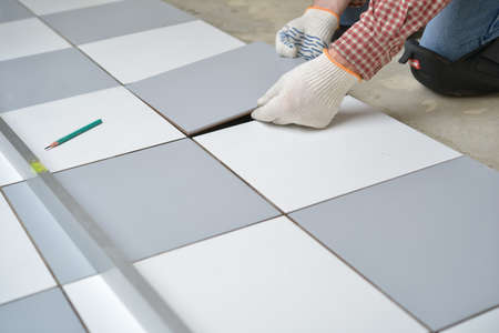 floor tiles: Tiler install ceramic tiles on a floor Stock Photo