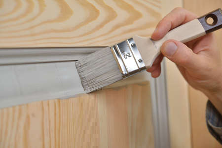Contractor painting a wooden door Standard-Bild