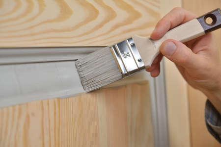 Contractor painting a wooden door 版權商用圖片