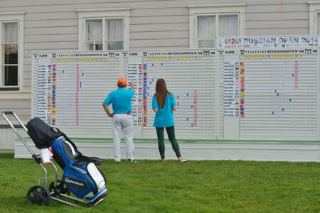 Tseleevo, Moscow region, Russia - July 24, 2014: Golfer under the scoreboard of the M2M Russian Open in the Tseleevo Golf & Polo Club. This international golf tournament is the stage of the European Tour Editorial