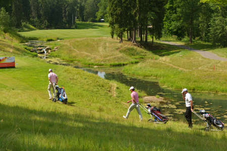 Tseleevo, Moscow region, Russia - July 24, 2014: Golfers on the golf course in the Tseleevo Golf & Polo Club during the M2M Russian Open. This international golf tournament is the stage of the European Tour Editorial