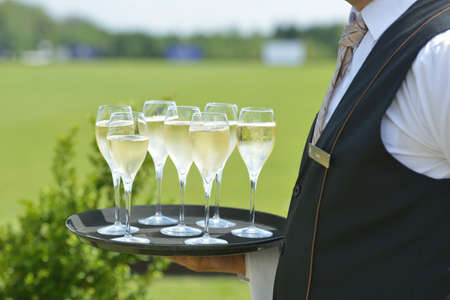 Tseleevo, Moscow region, Russia - July 26, 2014  Waiter holds the tray with champagne for the guests of the British Polo Day  It was the second British Polo Day in Russia Stock Photo