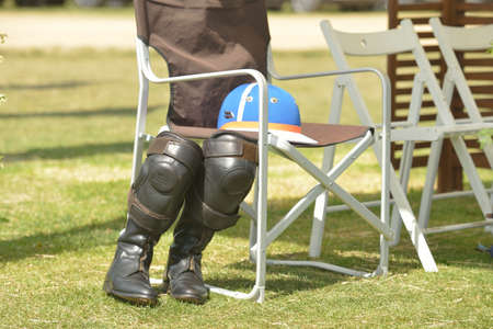 Tseleevo, Moscow region, Russia - July 26, 2014  Equestrian helmet and riding boots with kneepads on the folding chair during the British Polo Day  It was the second British Polo Day in Russia Stock Photo