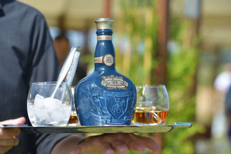Tseleevo, Moscow region, Russia - July 26, 2014  Waiter offers the whiskey Royal Salute to the guests of the British Polo Day  This brand of Scotch whisky produced by Chivas Brothers