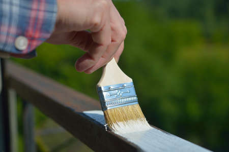 Man painting a guard rail on a balcony photo