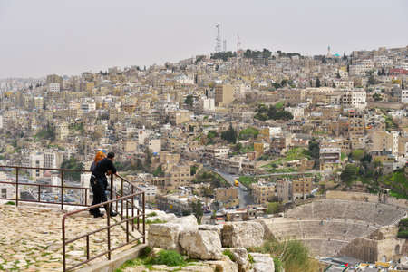 bewonderen: Amman, Jordan - March 17, 2014  Tourists admire the view to the Roman Theatre from the Citadel hill  Built in the II century, it could seat about 6,000 people Redactioneel