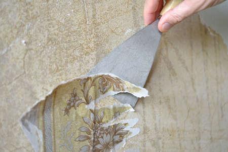 Het oude behang verwijderen van de muur met behulp van troffel Stockfoto - 30819749