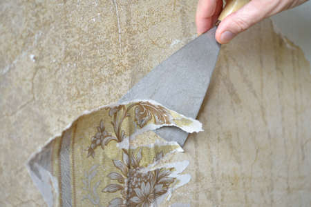 Removing the old wallpaper from the wall using trowel photo