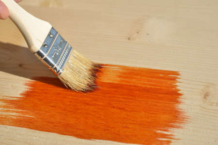 wood stain: Painting the plank with wood stain Stock Photo