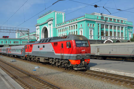 accommodate: Novosibirsk, Russia - August 25, 2014: Passenger train arriving on the main railroad station of Novosibirsk. The building completed in 1939 and can accommodate up to 3.9 thousand passengers