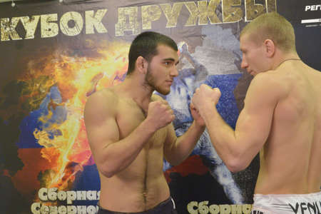 novosibirsk: Novosibirsk, Russia - November 7, 2014: Kasum Kasumov (left) and Alexander Matmuratov posing against the poster of the Friendship Cup, The competitions include 10 kinds of martial arts