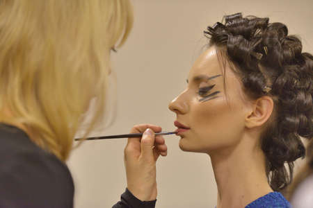 Novosibirsk, Russia - November 15, 2014: Model during makeup application before the fashion parade during Novosibirsk Fashion Week. The event was held under the motto High Fashion & High Classics Editorial
