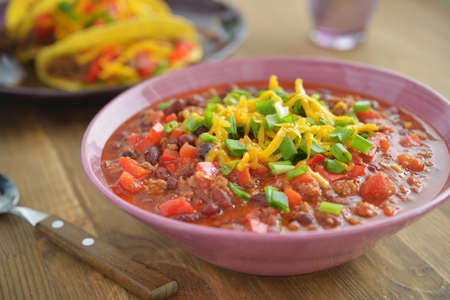 Chili con carne with Cheddar cheese and green onion photo