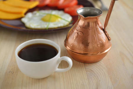 cezve: Cup of Turkish coffee and cezve against a breakfast