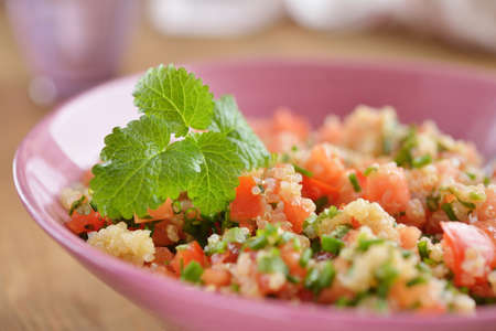 tabbouleh: Tabbouleh with quinoa, tomato, chives, and mint. Selective focus on the mint leaf