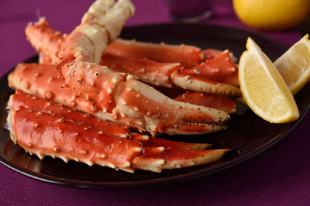Red king crab legs with lemon on a plate Stock Photo