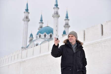 tatarstan: Man making selfie using smartphone against the mosque in Kazan, Russia
