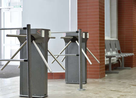turnstile: Turnstile controlling access to the building Stock Photo