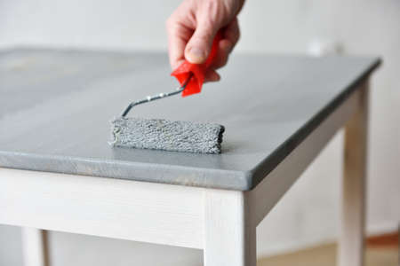 Painting a table using paint roller Stockfoto