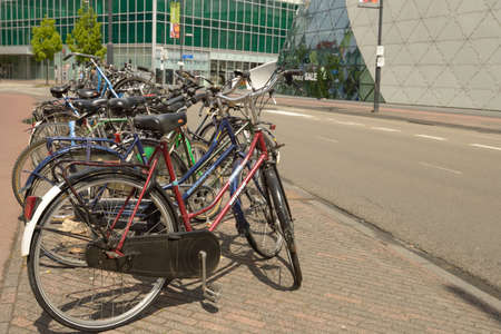 eindhoven: Eindhoven, Netherlands - June 23, 2013: Bicycle parking against the futuristic The Blob building. The bike is considered as an element of real Dutch life