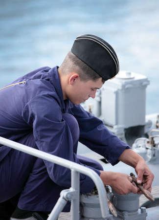 frigate: Sevastopol, Crimea, Ukraine - August 17, 2012: Seaman performs maintenance the torpedo tube on the Russian frigate Pytlivy. Built in Kaliningrad in 1981, the frigate included in the Black Sea Fleet since 1982