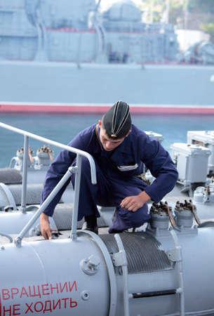 frigate: Sevastopol, Crimea, Ukraine - August 17, 2012: Seaman performs maintenance of  the torpedo tube on the Russian frigate Pytlivy. Built in Kaliningrad in 1981, the frigate included in the Black Sea Fleet since 1982
