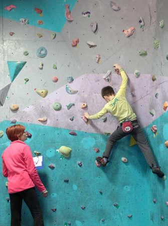 bouldering: Dnepropetrovsk, Ucraina - 11 APRILE 2015: Ragazzo compete durante la festa del boulder aperto Dnepr Montana Kids. Il festival organizzato dalla parete di arrampicata Montana e l'associazione locale degli sport estremi