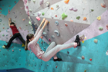 climbing wall: Dnepropetrovsk, Ukraine - April 11, 2015: Girls train during the open bouldering festival Dnepr Montana Kids. The festival organized by the climbing wall Montana and the local association of extreme sports