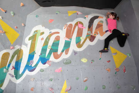 bouldering: Dnepropetrovsk, Ukraine - April 11, 2015: Girl trains during the open bouldering festival Dnepr Montana Kids. The festival organized by the climbing wall Montana and the local association of extreme sports