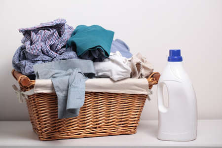 dirty clothes: Dirty clothes in the laundry basket and a bottle of detergent