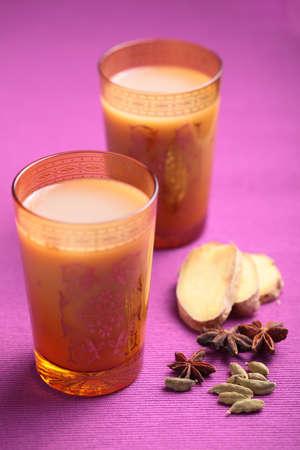 masala chai: Masala chai tea in yellow glasses and spices