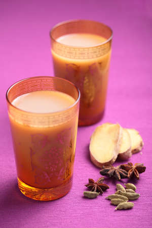 chai: Masala chai tea in yellow glasses and spices