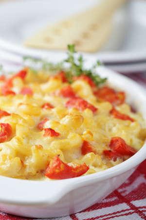 Macarrones y queso con tomate en un plato para hornear. Enfoque selectivo