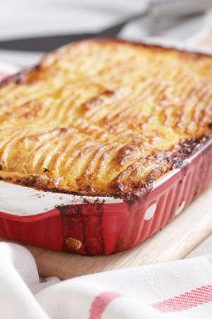 Cottage pie in a red baking dish Standard-Bild