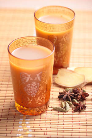 masala chai: Masala chai tea in yellow glasses and spices on a straw mat Stock Photo