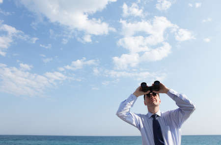 developement: Businessman with binoculars looking upward against a sea and skyscape