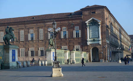 armory: Turin, Italy - January 11, 2013: People on the Piazza Castello against the building of Royal Armory. Since 1997, it included in UNESCO World Heritage list as part of Residences of the Royal House of Savoy