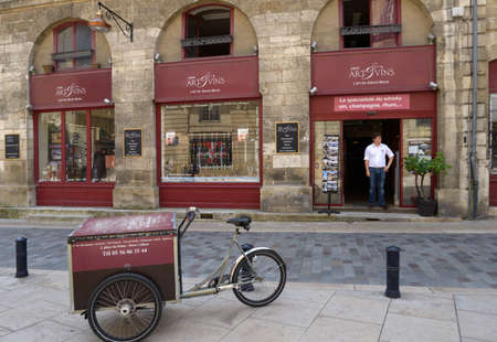 vins: Bordeaux, France - June 27, 2013: Man in doors of the cafe Art Et Vins on the Palace square. This wine trading house works only with authentic wines and offers quality services to clients