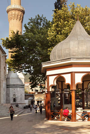 minarets: Bursa, Turkey - August 20, 2011: People make ablution near the Grand Mosque. Built in 1396-1399, the mosque has 20 domes and 2 minarets.