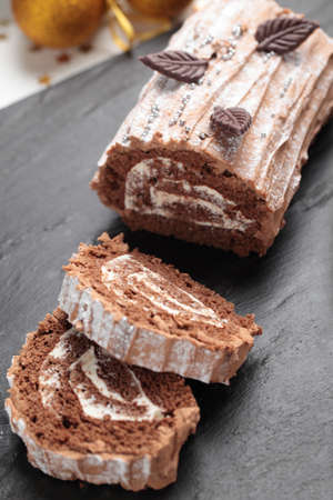 yule log: Yule log cake decorated with chocolate leaves on a Christmas table