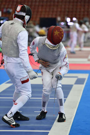 fencing foil: St. Petersburg, Russia - May 1, 2015: Szymon Kozlowski of Poland vs Haiwei Chen of China during the first day of competitions in 41th International fencing tournament St. Petersburg Foil. The tournament is the stage of FIE World Cup