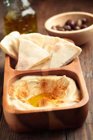 Hummus with sliced pita bread on a rustic table photo