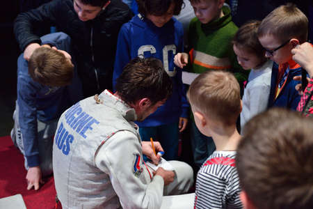 fencing foil: St. Petersburg, Russia - May 2, 2015: Winner of the International fencing tournament St. Petersburg Foil Dmitry Rigin of Russia gives autographs to children. The tournament is the stage of the FIE World Cup Editorial