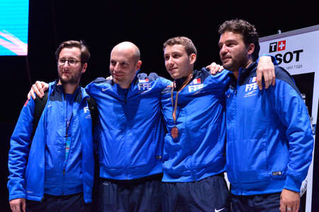 award ceremony: St. Petersburg, Russia - May 2, 2015: Bronze medalist of International fencing tournament St. Petersburg Foil Vincent Simon of France with his coaches after award ceremony. The tournament is the stage of FIE World Cup Editorial
