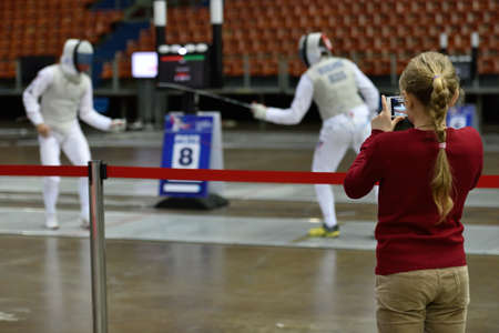 fencers: St. Petersburg, Russia - May 3, 2015: Girl make photo of Russian fencers training during the International fencing tournament St. Petersburg Foil, The tournament is the stage of FIE World Cup