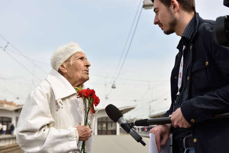 postwar: St. Petersburg, Russia - May 7, 2015: WWII veteran is interviewed by a journalist during the parade of steam locomotives. The event recreates the atmosphere of the postwar years for veterans and spectators