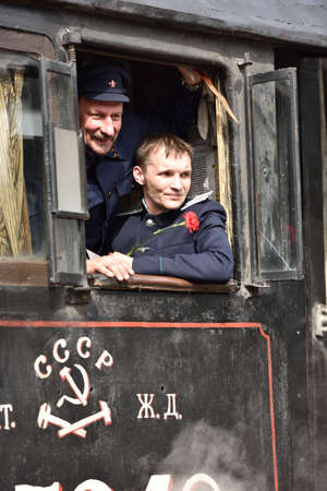 steam locomotive: St. Petersburg, Russia - May 7, 2015: Machinists in the cab of steam locomotive during the parade dedicated to the WWII Victory Day. The event recreates the atmosphere of the postwar years for veterans and spectators Editorial