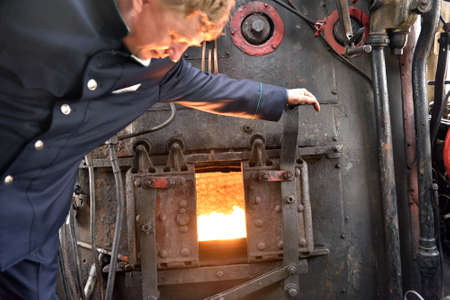 machinist: St. Petersburg, Russia - May 7, 2015: Machinist assistant opens the firebox of a steam locomotive. The parade of steam locomotives dedicated to the WWII Victory Day Editorial