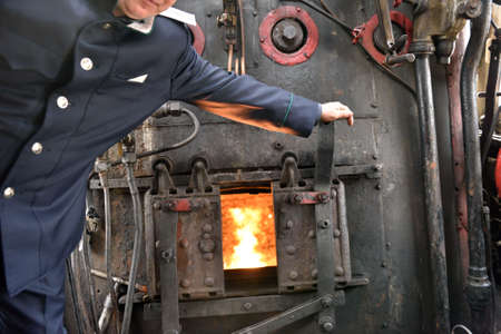 machinist: St. Petersburg Russia  May 7 2015: Machinist assistant opens the firebox of a steam locomotive. The parade of steam locomotives dedicated to the WWII Victory Day Editorial